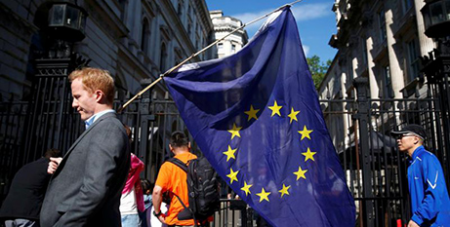 A man carries a European Union flag in London the day after voters in the United Kingdom decided to leave the EU (CNS/Neil Hall, Reuters)