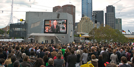 A crowd in Federation Square, Melbourne, watches Kevin Rudd deliver the apology (Flickr/virginiam)