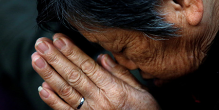 Woman prays at a 2013 Mass in Tianjin, China (CNS/Kim Kyung-Hoon, Reuters)