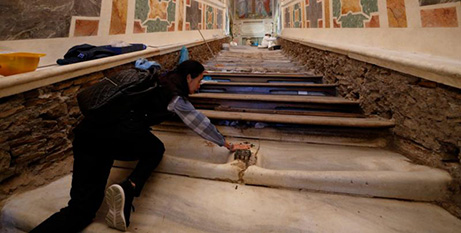 Mei Wen of Perth touches an area of the Holy Stairs where Jesus is believed to have fallen (CNS/Paul Haring)