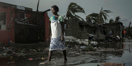 A woman walks through floodwaters in the aftermath of Cyclone Idai in Beira, Mozambique  (CNS/Josh Estey, Care International via Reuters)