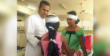 Fr Basil Rohan Fernando with people injured in the Easter Sunday attack in Sri Lanka (Missio UK)
