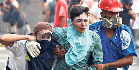 An injured demonstrator is assisted during a violent protest in Caracas, Venezuela on April 30 (CNS)
