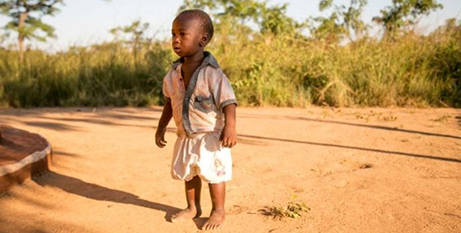 A child outside his home in the Zambian village of Ndombi (CNS/Michael Stulman, CRS)