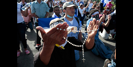 People pray in front of police blocking the entrance to a Managua church on Saturday (CNS/Oswaldo Rivas)