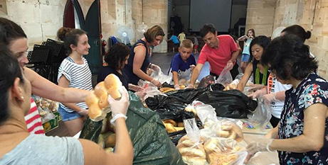 Volunteers from Fr John Therry School pack bread at the Balmain outreach centre (SBS News)