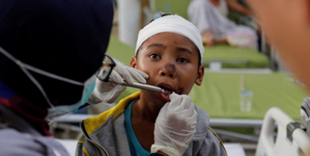 Paramedics treat a child injured in the Lombok earthquake (CNS/Beawiharta, Reuters)
