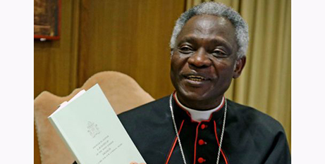 Cardinal Peter Turkson with a copy of Laudato Si