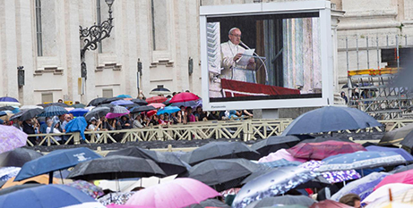 Pilgrims watch Pope Francis on a large screen as he leads the Angelus at the Vatican on Sunday (CNS/Claudio Peri, EPA)