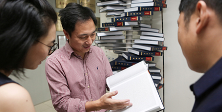 "Researcher He Jiankui shows ""The Human Genome"" a book he edited in 2016 (CNS/Reuters)"