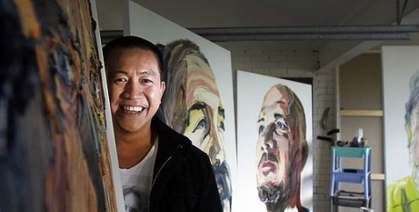 Anh Do stands with his portrait
