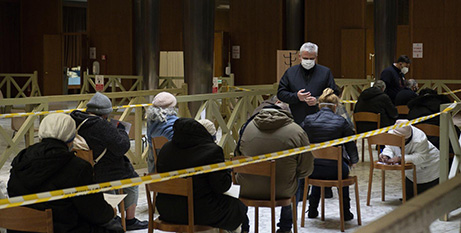 Cardinal Konrad Krajewski (standing) assists as homeless people receive the first dose of the COVID-19 vaccine in the atrium of the Paul VI hall at the Vatican yesterday (CNS/Vatican Media)