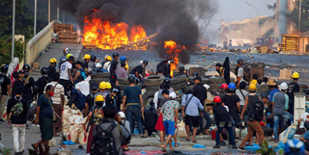 Protesters at a barricade made from tyres clash with security forces in Yangon on Tuesday (CNS/Reuters)