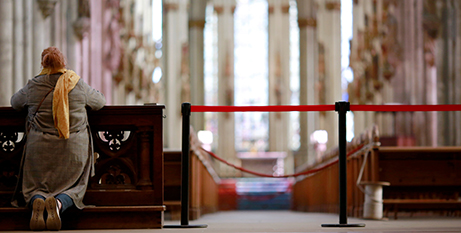 A woman prays beside a barrier inside the Cologne Cathedral in Germany (CNS photo/Thilo Schmuelgen, Reuters)