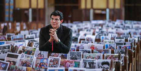 A priest prays during Mass with photos of his parishioners taped to the pews in the Shrine of Our Lady of Guadalupe in Curitiba, Brazil, on Saturday (CNS/Rodolfo Buhrer, Reuters)