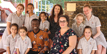Gemma Sisia (front), Godwin Silayo and Maddie Kelly (back) with St Aloysisus students (The Southern Cross)