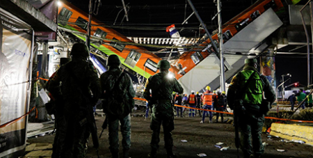 Soldiers stand guard as rescuers work at the site where an overpass for a metro partially collapsed on Monday (CNS/ Luis Cortes, Reuters)
