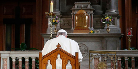 Pope Francis prays in front the tabernacle and a candle lit in memory of victims of sexual abuse at St Mary's Pro-Cathedral in Dublin last year (CNS/Paul Haring)