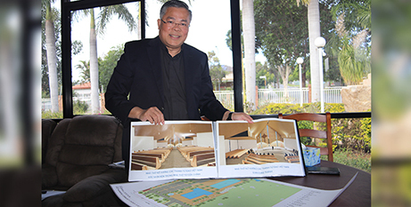 Fr Joseph Vu with plans for the new Vietnamese church in Inala (The Catholic Leader/Joe Higgins)