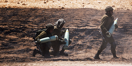 Israeli soldiers carrying artillery shells on the border between Israel and the Gaza Strip on Friday (CNS/Amir Cohen, Reuters)
