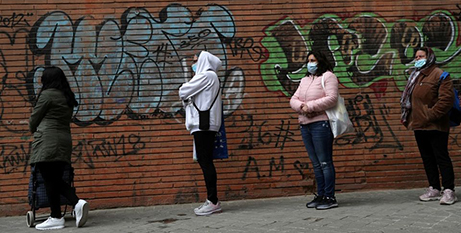 People in Madrid line up to receive donated food during the COVID 19 pandemic (CNS/Susana Vera, Reuters)