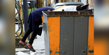 A man searches through a dumpster in Lebanon in April.  (CNS/Ali Hashisho, Reuters)