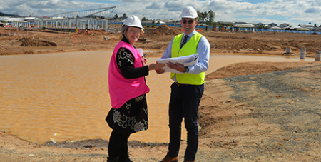 Dr Margaret Lee and principal Peter Edwards inspect building progress at San Damiano College in Yarrabilba (The Catholic Leader)