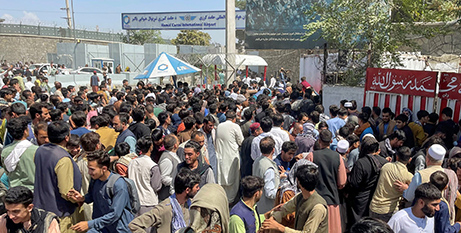 People try to get into Hamid Karzai International Airport in Kabul on August 16 (CNS/Reuters)