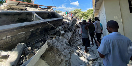 People inspect a house destroyed by the earthquake in Haiti (Caritas Haiti)