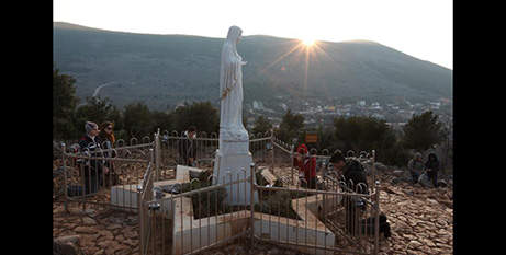 Pilgrims pray at a statue of Mary on Apparition Hill in Medjugorje, Bosnia-Herzegovina (CNS/Paul Haring)