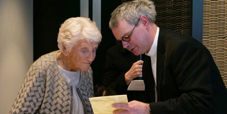 Eileen Piper shows Archbishop Peter Comensoli a photo of her daughter Stephanie (ABC News/Dylan Anderson)