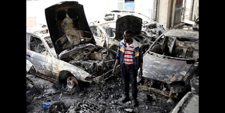 Nigerian Basil Onibo inspects the burned cars at his dealership in Johannesburg (CNS/Siphiwe Sibeko, Reuters)