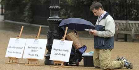 A pro-life activist prays outside a London abortion clinic (CNS/Olivia Harris, Reuters)
