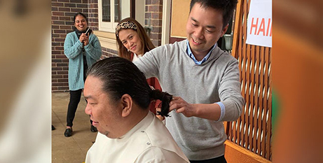 Deacon Tuan Anh Le cuts Fr Francis Belcina's hair (The Catholic Leader/Supplied)