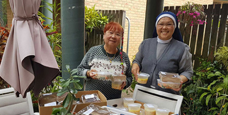 Sr Salvacion Bunao and volunteer Lita Espinosa with hot meals for the vulnerable of South Brisbane (Supplied)