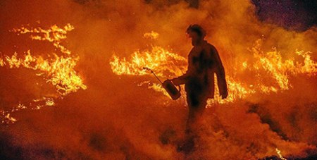 A lone firefighter walks into the flames to back burn the bushland while bushfires rage around Queensland and New South Wales (The Catholic Leader)