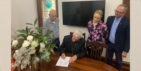 Plenary Council president Archbishop Timothy Costelloe SDB signs the official list of attendance for Plenary Council watched by scrutineers, from left, Damian Walsh, Gemma Thomson and Fr George Kolodziej SDS (ACBC)