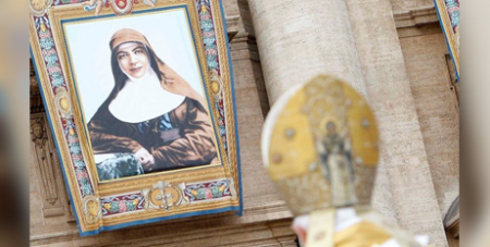 Pope Benedict XVI with a tapestry showing St Mary MacKillop at her canonisation at St Peter's Basilica on October 17, 2010 (CNS/Tony Gentile, Reuters)