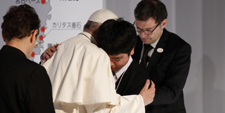 Pope Francis embraces a victim of the 2011 triple disaster in Tokyo yesterday (CNS/Paul Haring)